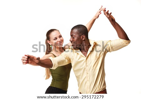 Young couple dances social Caribbean Salsa, studio shot isolated on white background. Positive human emotions. black african and Caucasian models - stock photo