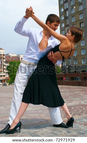 young couple dancing Latino dance against urban landscape - stock photo