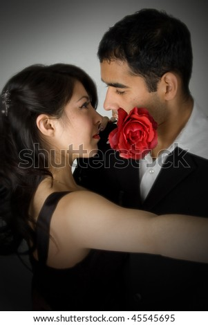 Young couple dancing with rose in mouth. - stock photo