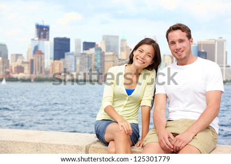 Young couple dating in New York. Portrait of multi-ethnic couple with Manhattan and New York City Skyline in background. Asian woman, Caucasian man tourists on Ellis Island, New York City, USA - stock photo