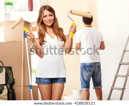 Young couple decorate their new apartment.Woman standing in front of camera. - stock photo