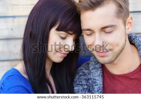 Young couple deeply in love standing close together with their foreheads touching and eyes closed enjoying a tender moment - stock photo