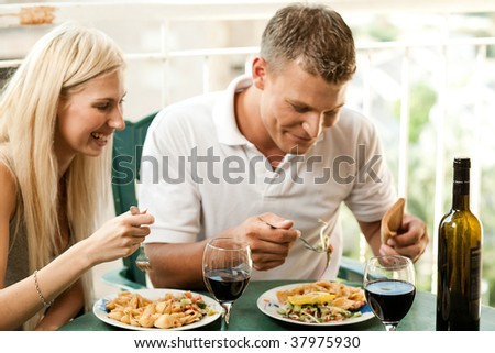 Young couple dining at home and having good time - stock photo