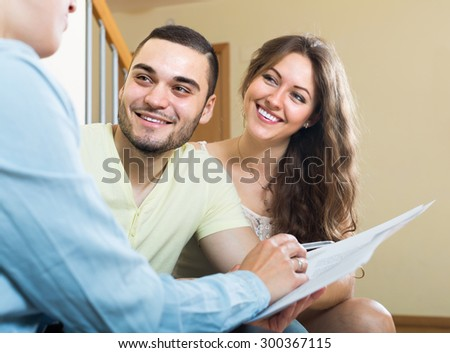 Young couple discussing details of private insurance with agent at home - stock photo