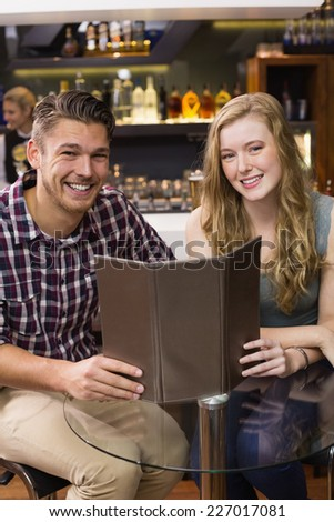 Young couple discussing the menu at the bar - stock photo