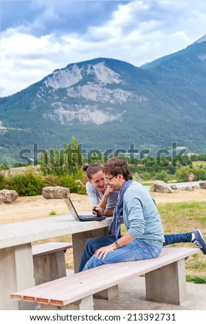 Young couple discussing travel plan and booking hotels on a laptop. Couple made a stop at viewpoint on the road in the Italian Alps - stock photo