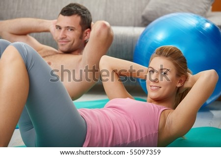 Young couple doing abdominal exercise lying on fitness mat at home in living room.