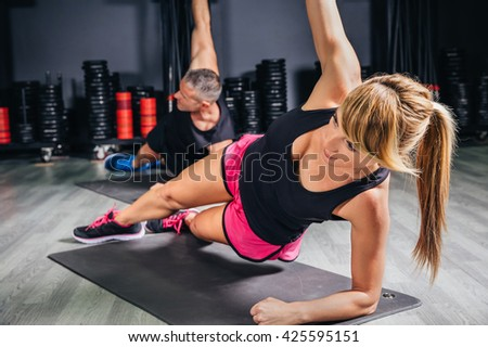 Young couple doing exercises in fitness class - stock photo