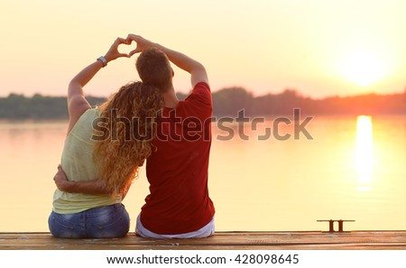 young couple doing heart shape with their hands on lake shore - stock photo