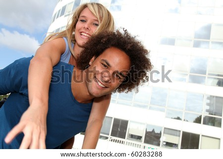 Young couple doing piggyback outside - stock photo