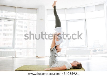 Young couple doing relaxation exercises in studio together - stock photo