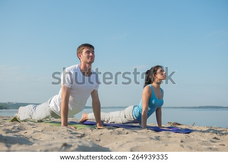 Young couple doing stretching yoga exercises with sea on the background - stock photo