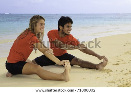 young couple doing yoga, exercise , and stretches on a hawaii beach