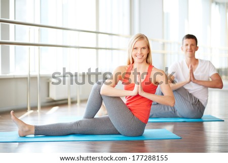 Young couple doing yoga exercises in fitness club - stock photo