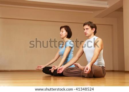 young couple doing yoga indoors - stock photo
