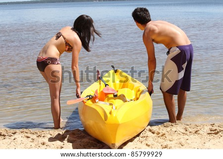 Young couple dragging their kayak onto the lake - stock photo