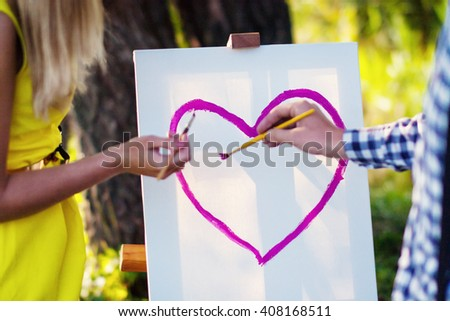 young couple draw heart - stock photo