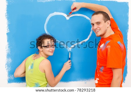 Young couple drawing a heart on the wall during home renovation