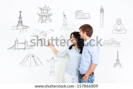 young couple dream think about vacation, holiday trip, man and woman planning draws travel around the world on white wall