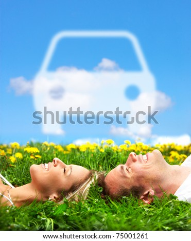 Young couple dreaming about a new car  under blue sky - stock photo