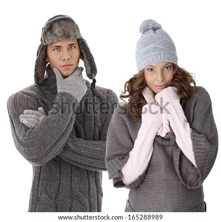 Young couple dressed for winter, wearing gloves and hat and warm sweater.