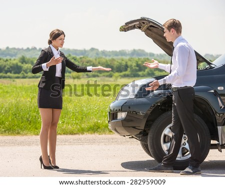 Young couple dressed formal having quarrel near a broken car on the roadside. - stock photo