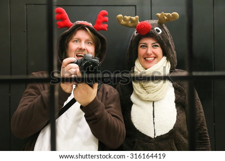 Young couple dressed up as two reindeer at Christmas in Madrid taking a selfie in an hotel mirror - stock photo