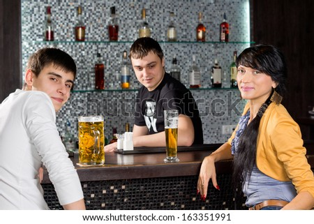 Young couple drinking at the bar with the barman turning and smiling at the camera as they spend a relaxing evening with friends - stock photo