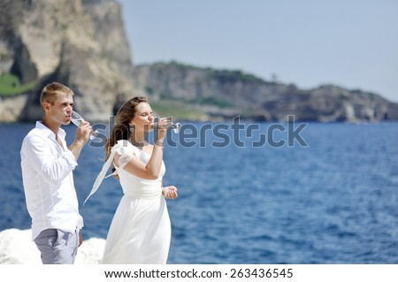 young couple drinking champagne in wedding day near sea of Naples, Italy