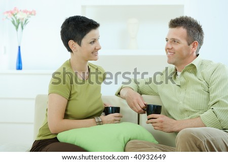 Young couple drinking coffee at home, sitting on couch, looking at each other, smiling.