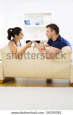 Young couple drinking coffee at home sitting on couch. Smiling and looking at each other. - stock photo