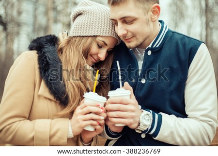 Young couple drinking coffee at the park.