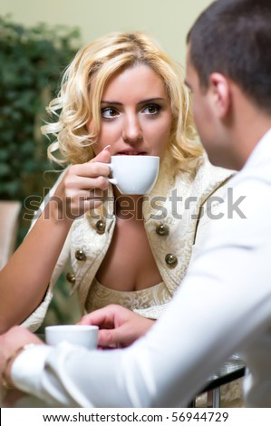 Young couple drinking coffee in a restaurant - stock photo