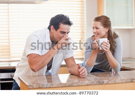 Young couple drinking coffee in the kitchen - stock photo