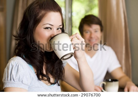 Young couple drinking coffee in their kitchen - stock photo