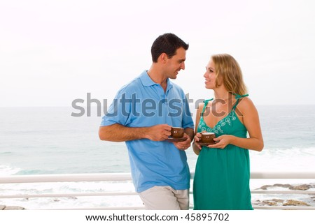 young couple drinking coffee on balcony, background is beautiful sea view