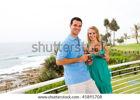 young couple drinking coffee on balcony, background is beautiful sea view - stock photo