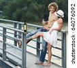 Young couple drinking on a bridge - stock photo