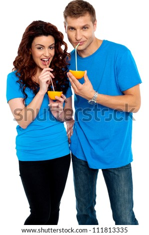 Young couple drinking orange juice together, sipping with straw - stock photo