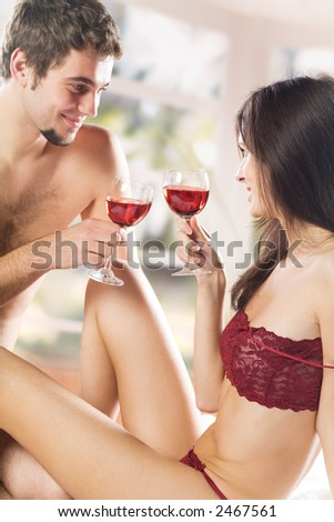 Young couple drinking red wine on the bed in bedroom - stock photo