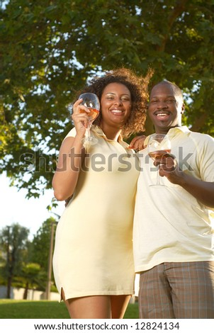 Young couple drinking wine and having fun outside - stock photo