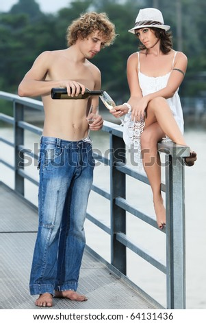 Young couple drinking wine on a bridge