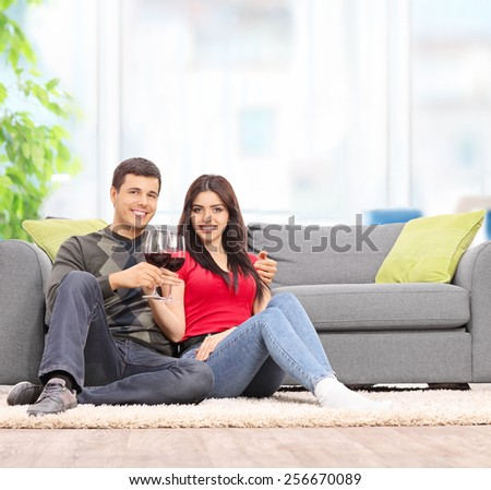 Young couple drinking wine seated by a sofa at home shot with tilt and shift lens - stock photo