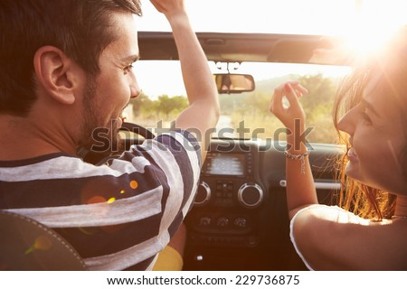 Young Couple Driving Along Country Road In Open Top Car - stock photo