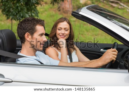 Young couple driving in a silver convertible through the countryside in sunshine - stock photo