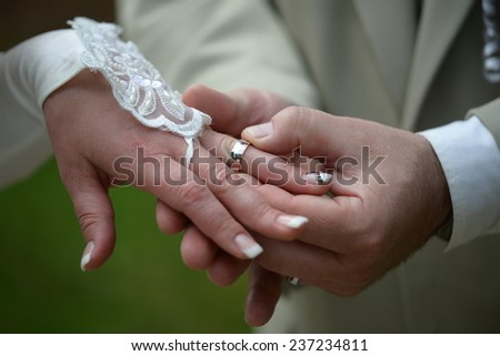 Young couple during putting on the wedding ring