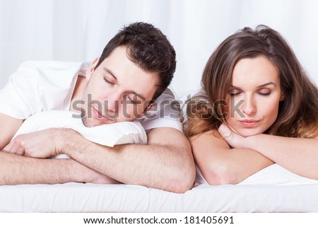Young couple during sleeping in their bed - stock photo