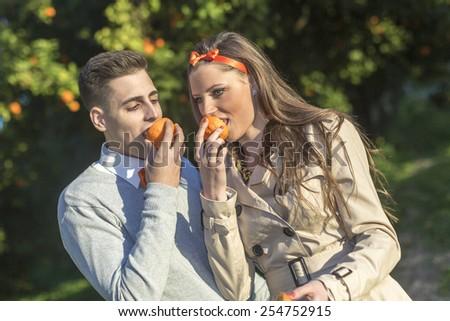 young couple eat orange - stock photo