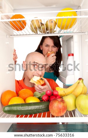 Young couple eating and looking at healthy fruit and vegetable in modern refrigerator, isolated on white background. - stock photo