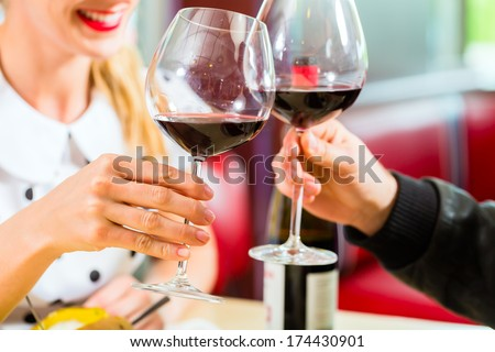 Young couple eating fast food and drinking red wine in a American retro fast food diner - stock photo
